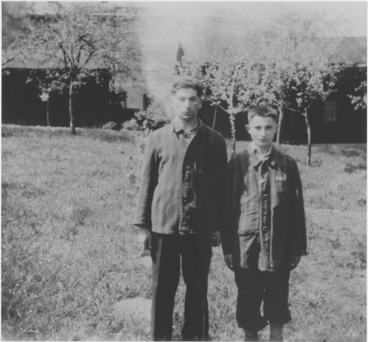 A Jewish father and son pose in their concentration camp uniforms soon after their liberation.  Pictured at the left is Carki Cukier, a cousin of Helen Sztelman Laudon. Carki and his son were imprisoned at the Skarzysko Kamienna factory labor camp during the war.