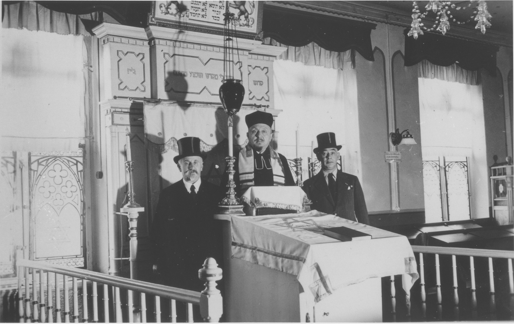 Three synagogue officials, including the rabbi and cantor, pose on the bimah [podium] in the sanctuary of the Striegau synagogue.