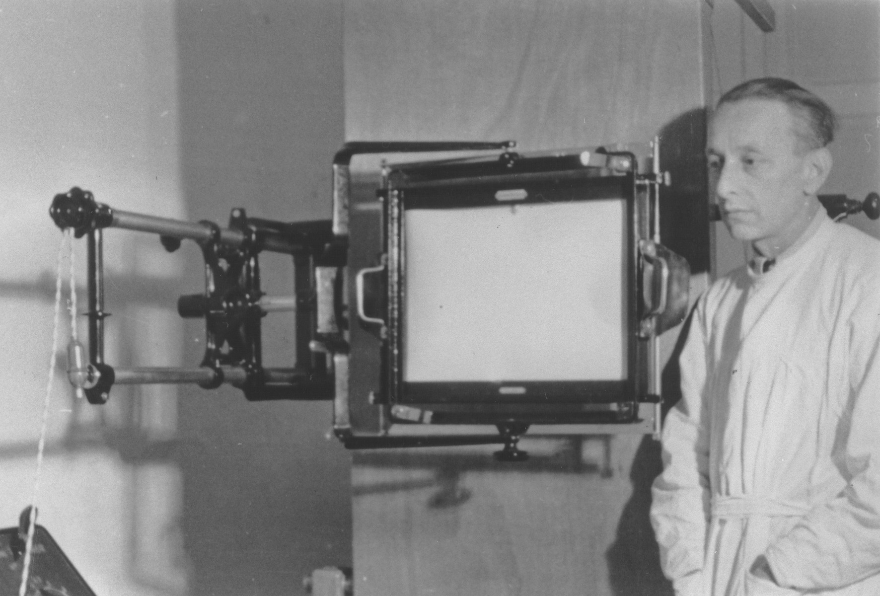 Jewish refugee, Dr. Mendel Kleinman, stands next to an x-ray machine in the hospital in Turka nad Stryjem.