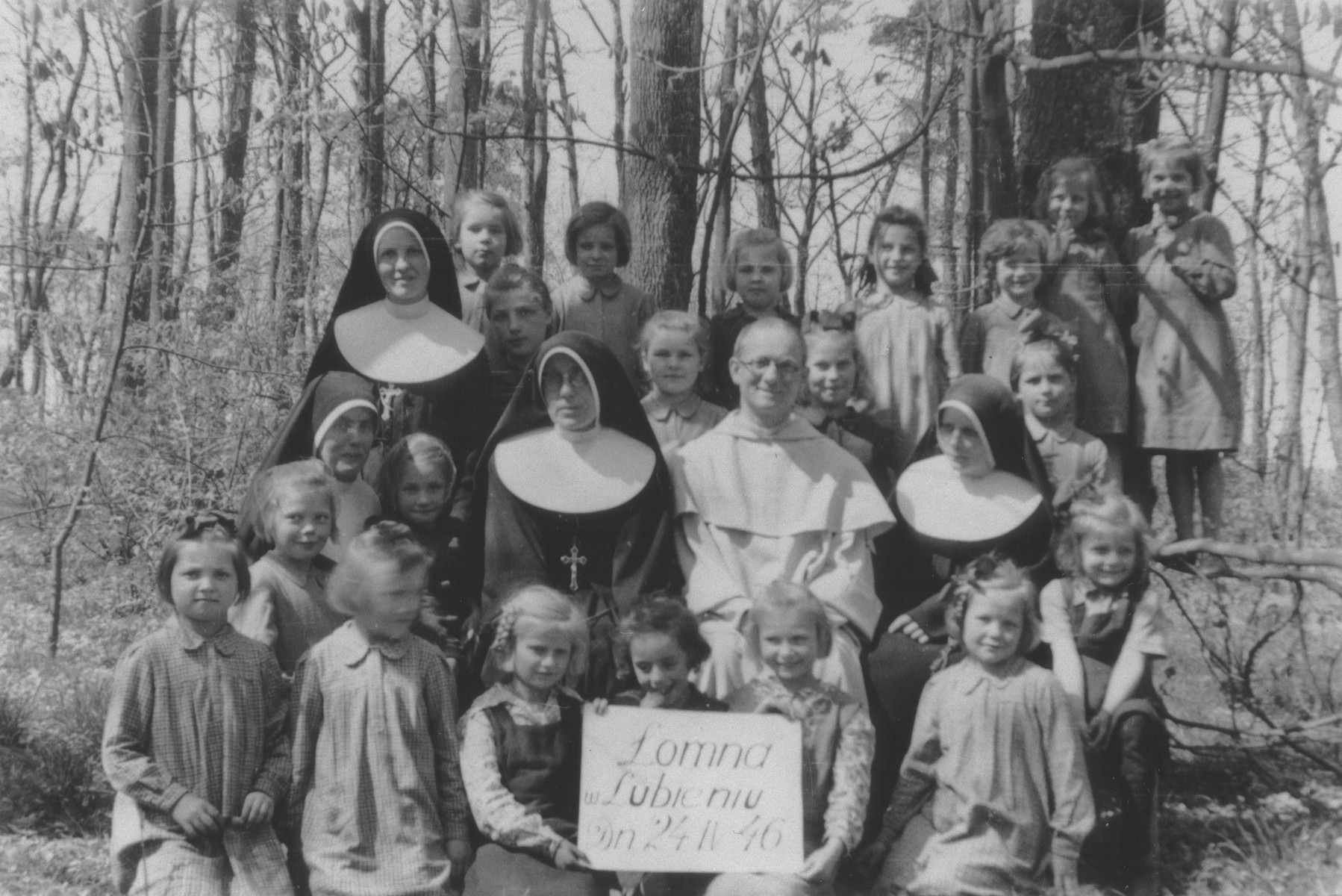 A priest and several nuns pose with a group of children at a Franciscan convent school in Lomna, Poland where Jewish children were hidden during the German occupation.  Among those pictured are Tereska, a Jewish girl who remained at the convent after the liberation when no one came to claim her (front row, center); Sister Blanka Pigowska (second row from the front, far right); Sister Tekla Budnowska (second row from the front, thrid from the right);and Sister Zofia Olszewska (second row from the front, far left).