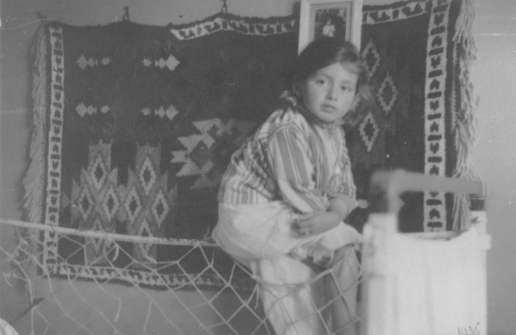 Portrait of a young Jewish girl, Lida Kleinman sitting in her room in Lacko, Poland.