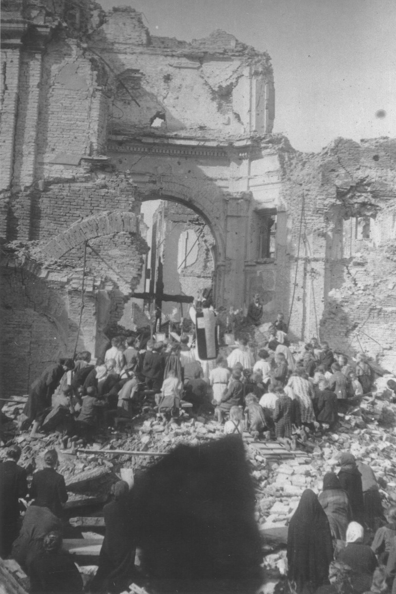 "A priest conducts mass among the ruins of the Franciscan convent on Zakroczymska Street in Warsaw where Jewish children were hidden during the German occupation.  The inscription on the back of the photograph reads, ""There are more than 1,000 dead buried beneath the rubble."""