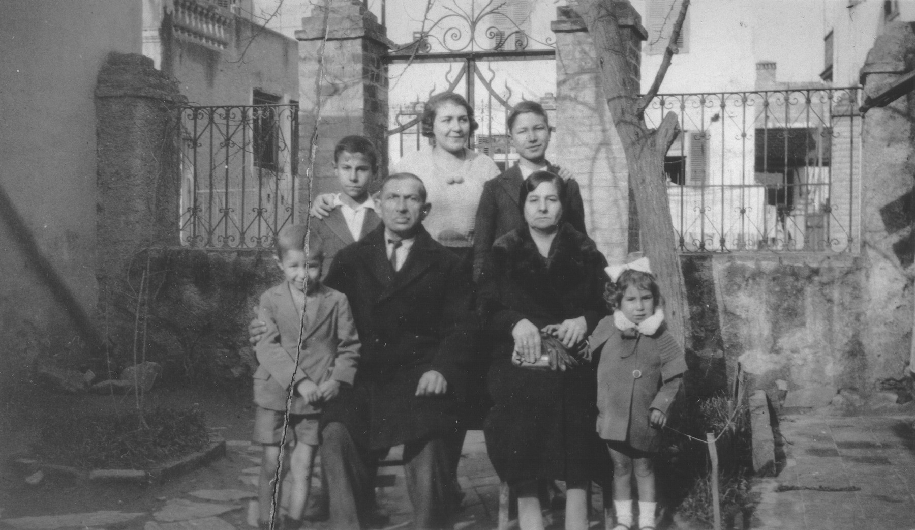 Portrait of the Beraha family in the courtyard of their home in Salonika.    Pictured are Eliahu and Sol Beraha (center) and their children: Yeshua (left), Alberto (back row, left), Miriam (back row, center), Baruch (back row, right) and a niece named Estrea (lower right).