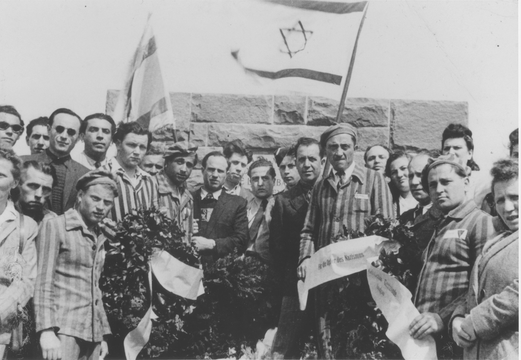 On the occasion of the first anniversary of the liberation of the Dautmergen concentration camp, Jewish survivors wearing concentration camp uniforms and carrying Zionist flags, bring wreaths to lay at the site.  Among those pictured is Kiwa Dajches (center, wearing light colored suit and dark tie).  Dautmergen, a subcamp of Natzweiler, operated from August 1944 until April 1945.