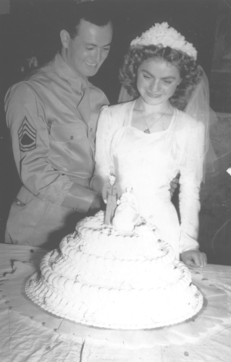 A Jewish bride and groom pose cutting their wedding cake.  Pictured are Harry Jagoda with his Yugoslavian Jewish bride, Florica Kabilio.