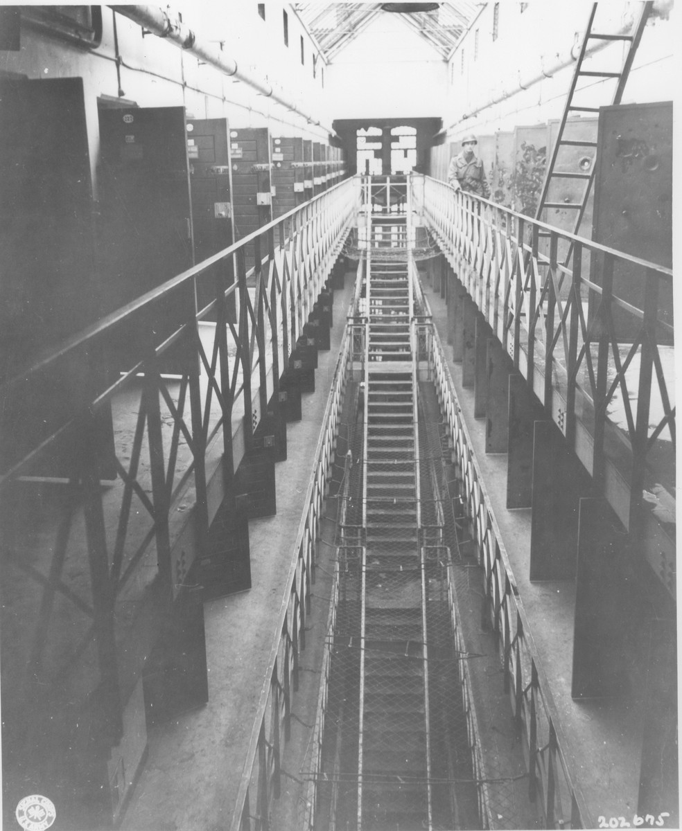 The interior of the Gestapo prison in Koeln.    Prisoners were forced to run these stairs while they were whipped by guards.  Prisoners supposedly stripped the paint from the doors next to which the American officer is standing as a result of going mad from Allied air raids.