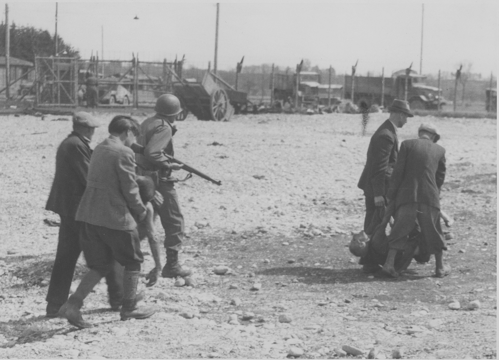 German civilians from the neighboring town of Hurlach are forced to carry bodies to a mass grave for burial.
