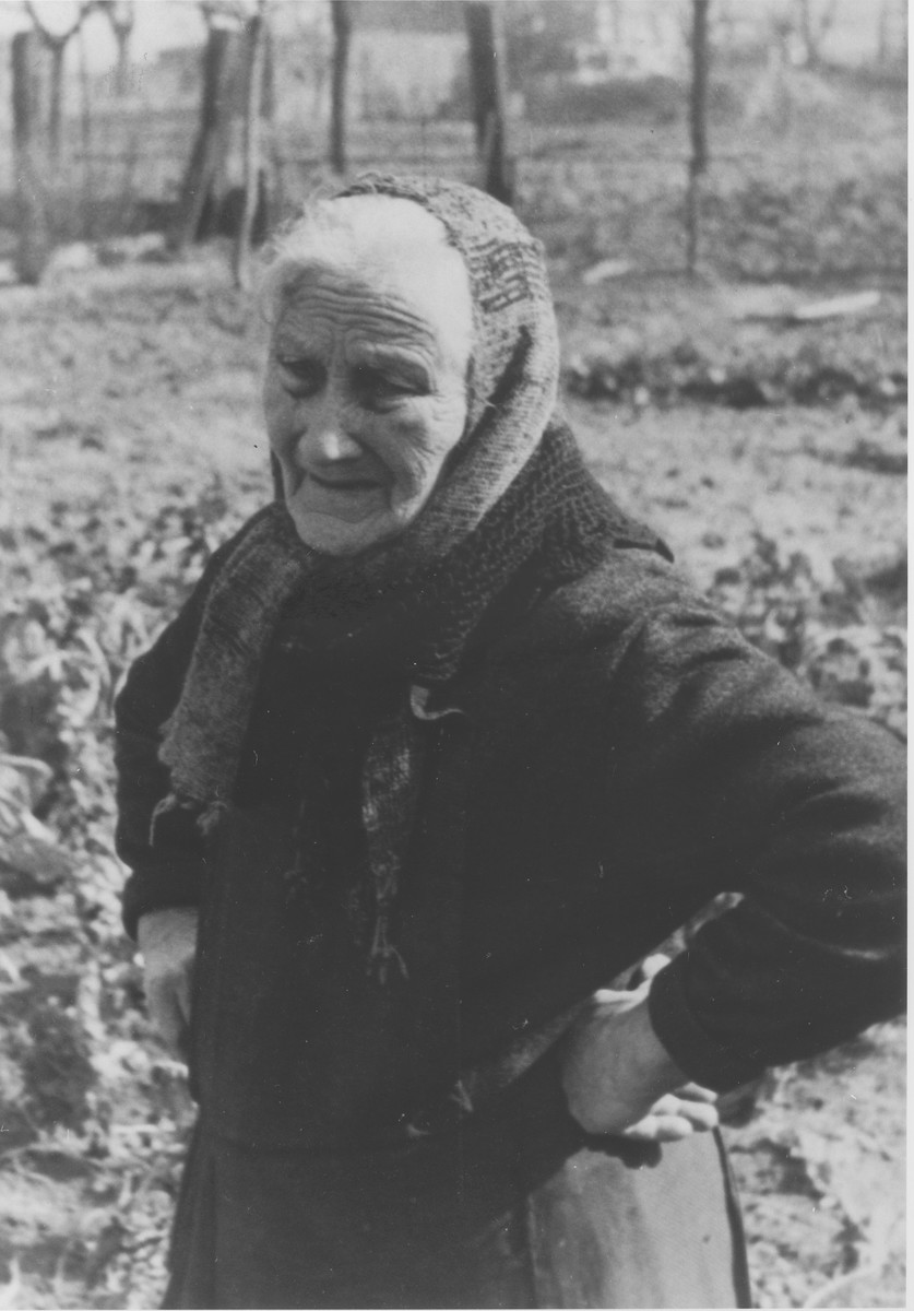 Portrait of an elderly Jewish woman standing in the garden of her farm.  Pictured is Dina Rueb (1851-1936).
