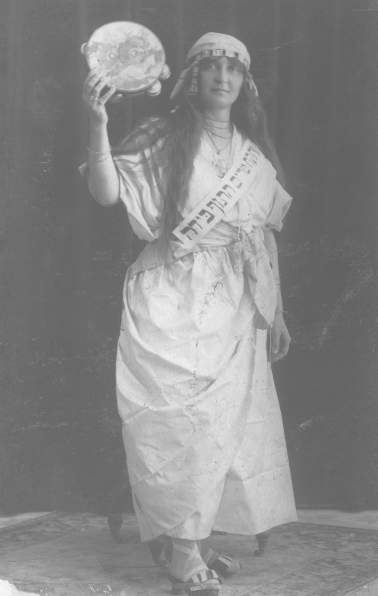 A young Jewish woman dressed up for Purim as the biblical figure Miriam, poses with a tambourine.  Pictured is one of the siblings of Rosa Altarac from Vlasenica, Bosnia.
