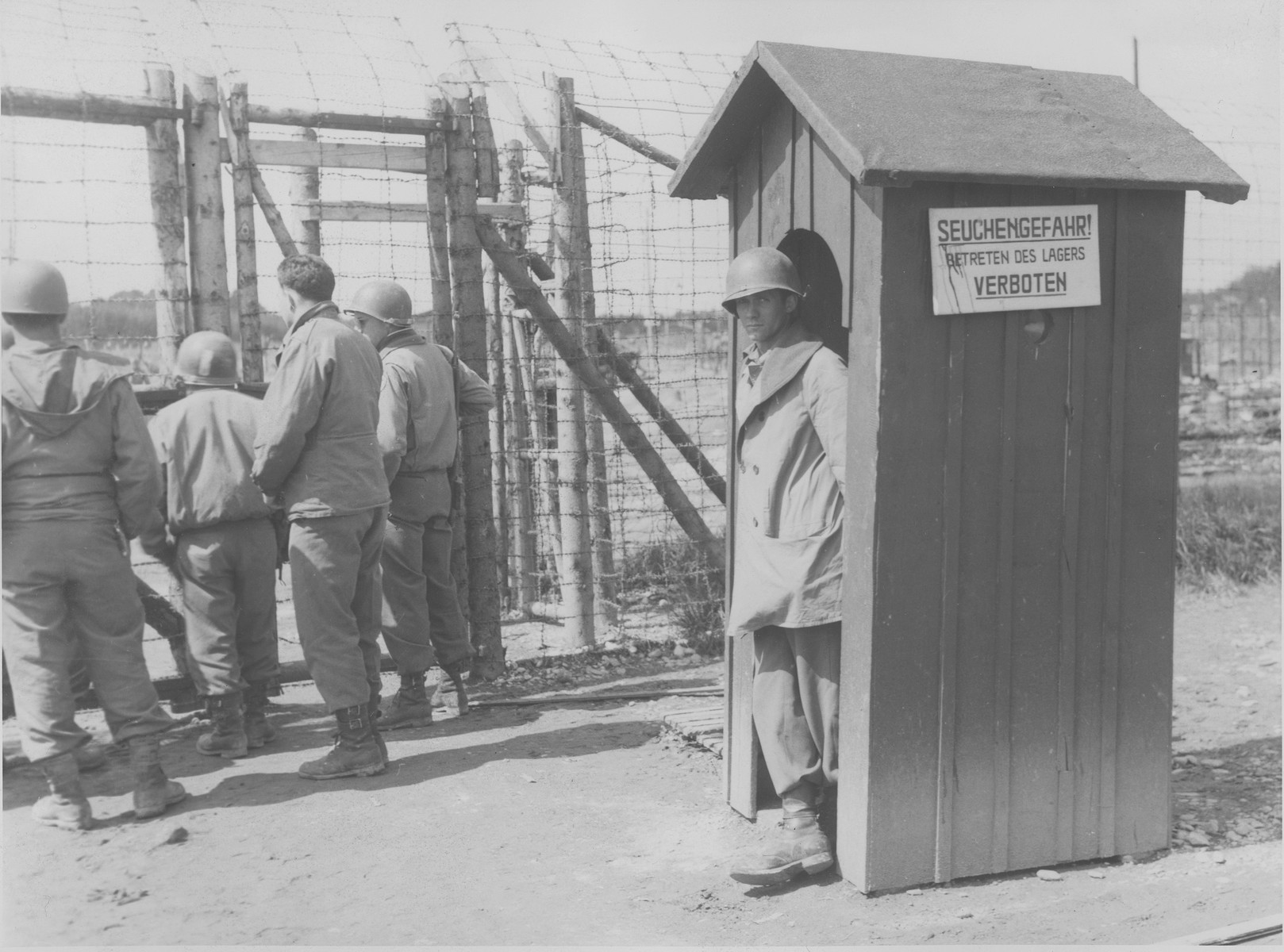American soldiers stand by the main entrance to the Kaufering IV concentration camp.