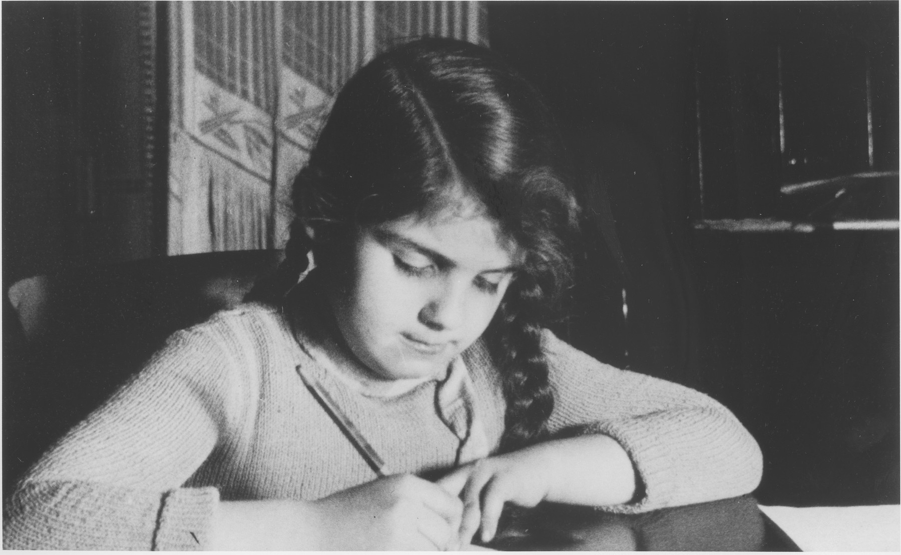 A young Jewish girl, Ann Hellman, writes her lessons at her home in Guntersblum, Germany.