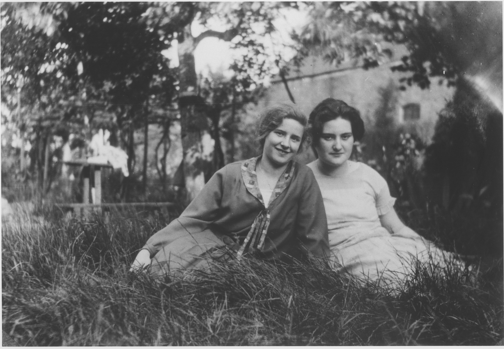 Two Jewish teenage friends sit outside in the grass.  Pictured are Hede Rube (left) and Emmi Schedel.