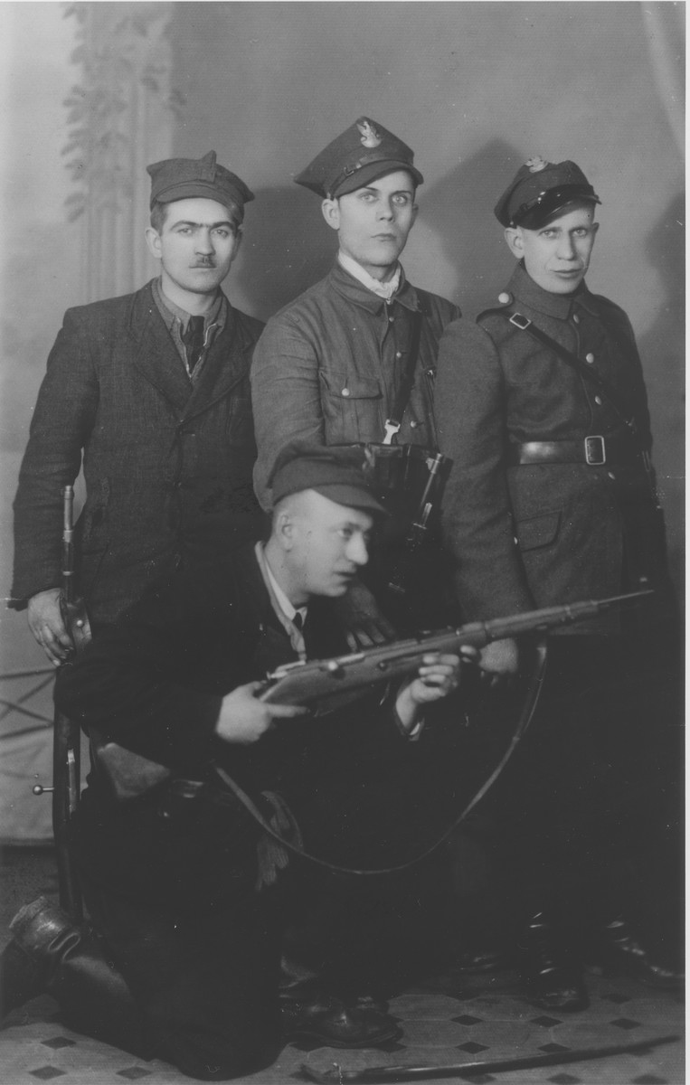 Jewish survivor, Wolf Laudon, poses with members of his Polish military police unit.    Wolf is kneeling in front holding a rifle.