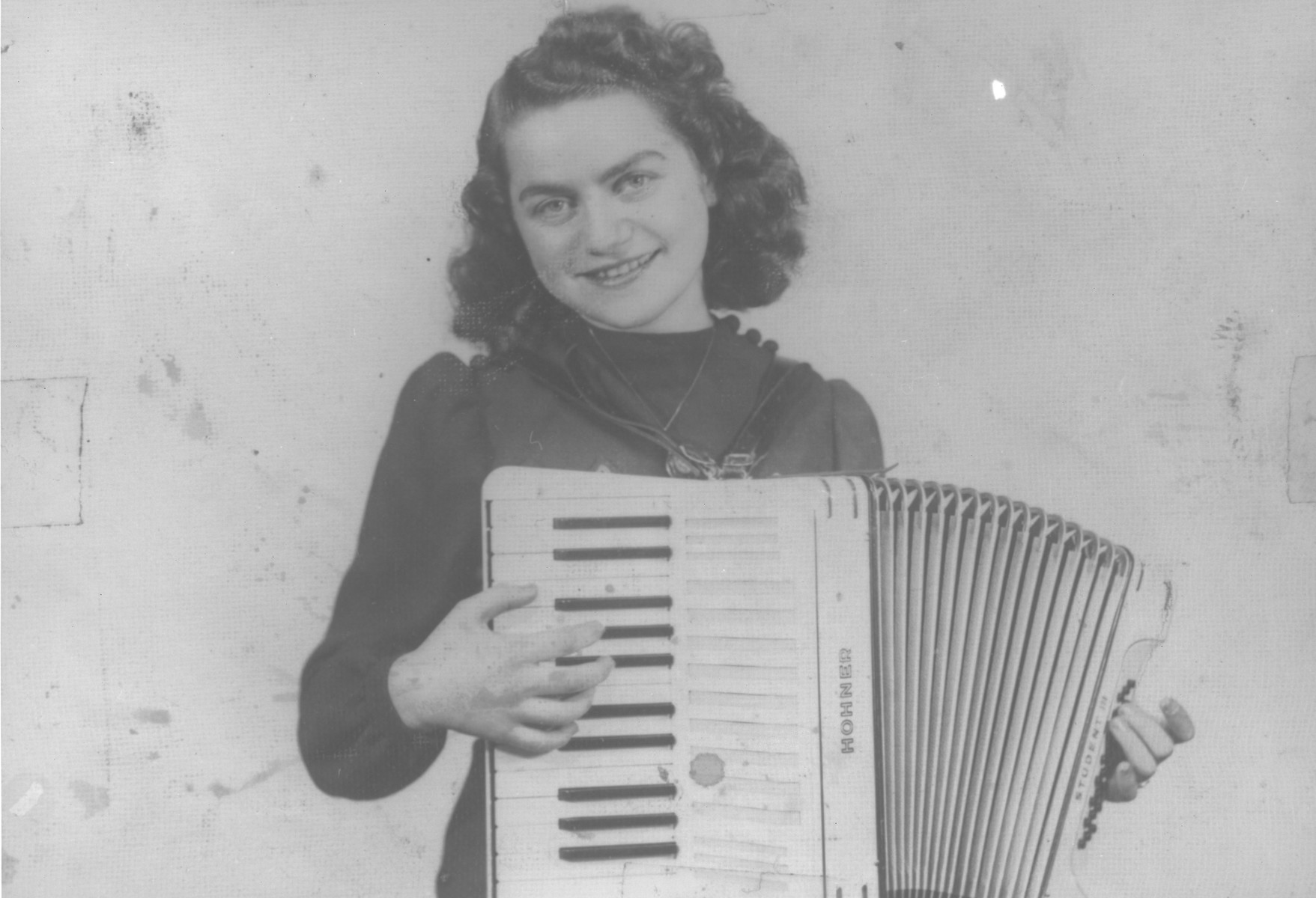 A young Jewish woman, Florica Kabilio, playing her accordion.
