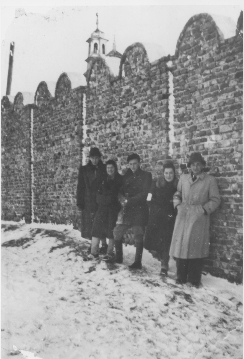 Manek D. Springut-Werdiger (center) stands with a group of friends against a section the Krakow ghetto wall.