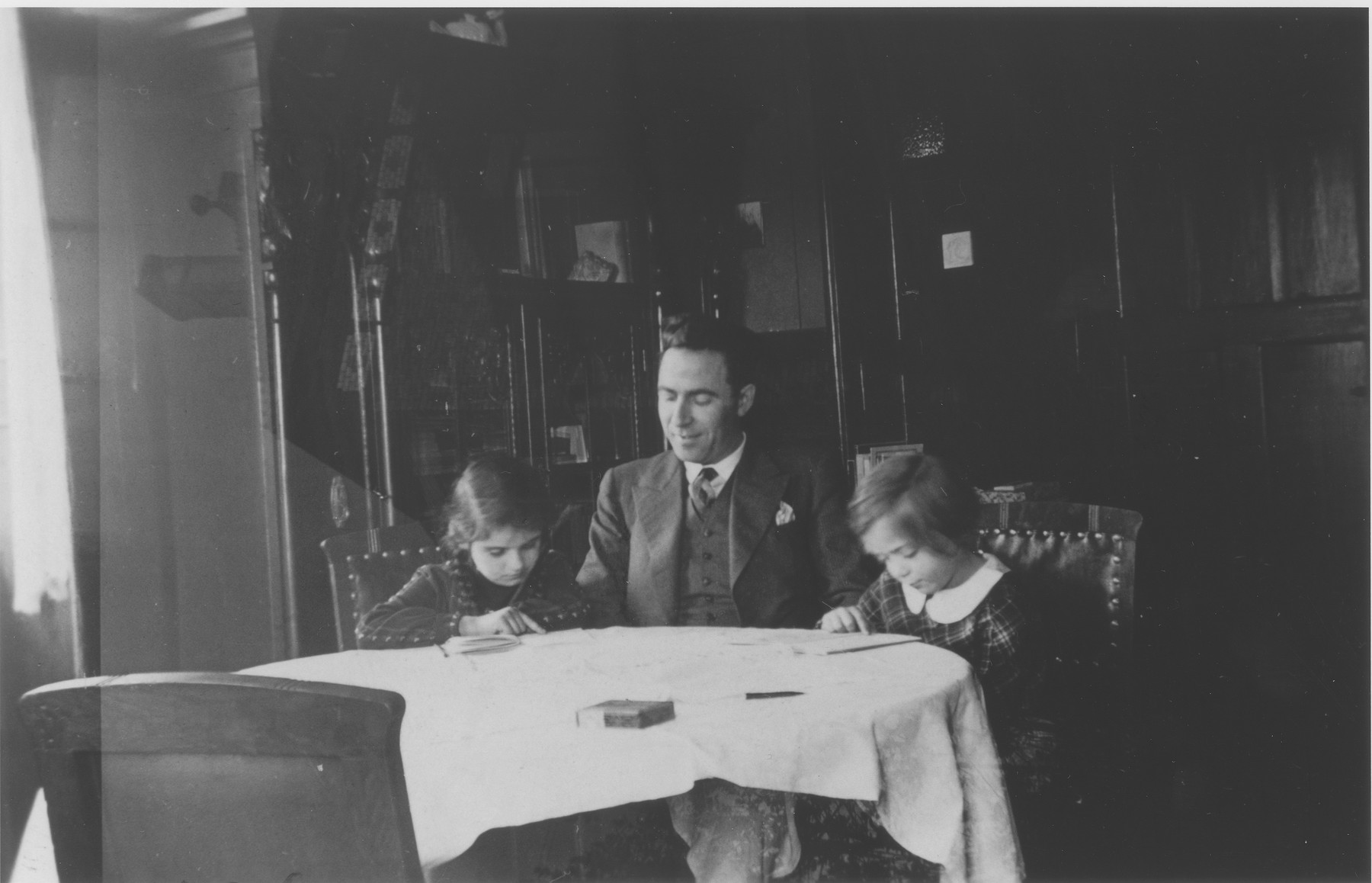 A Jewish religion teacher tutors two young girls in the dining room of a private home in Guntersblum, Germany.  Pictured from left to right are Ann Hellman, Carl Hartogsohn and Inge Seeman.