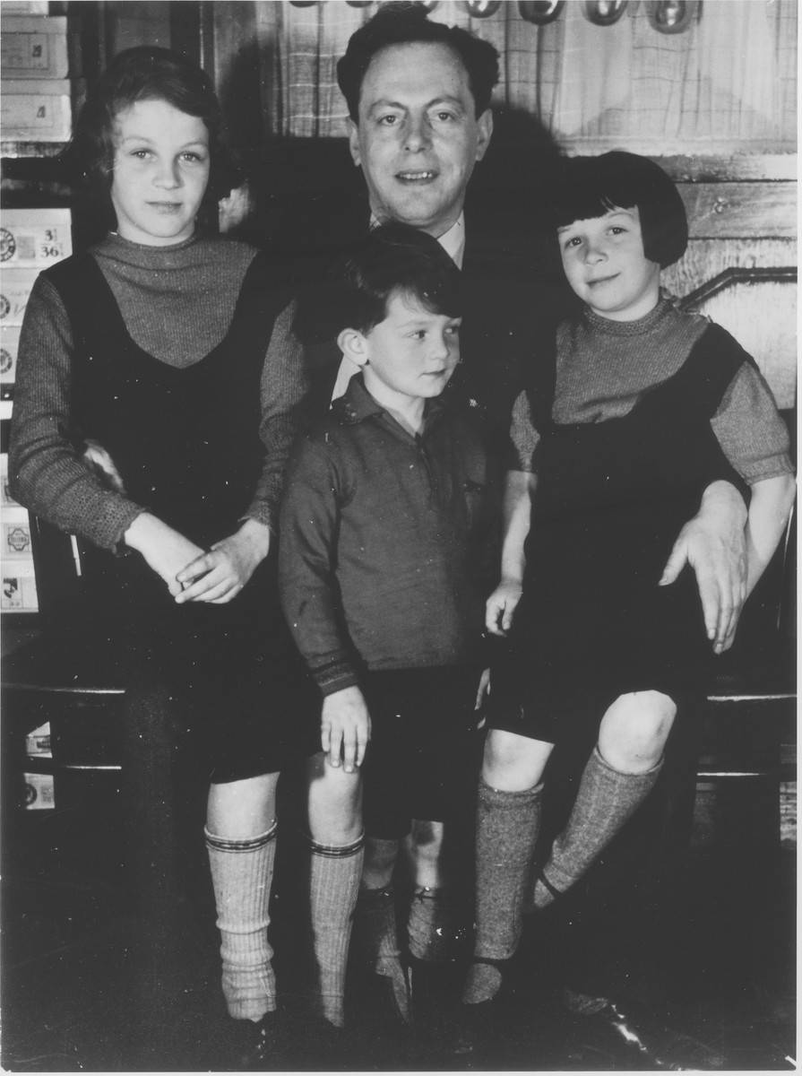 Leo Fraenkel poses with his nieces and nephew in the Erlanger shoe and dry goods store in Guntersblum, Germany.  The children pictured are Margo, Fritz and Hannelore Erlanger, the children of store owner, Lothar and Minna (Heis) Erlanger.  Leo Fraenkel was married to Lothar's sister.