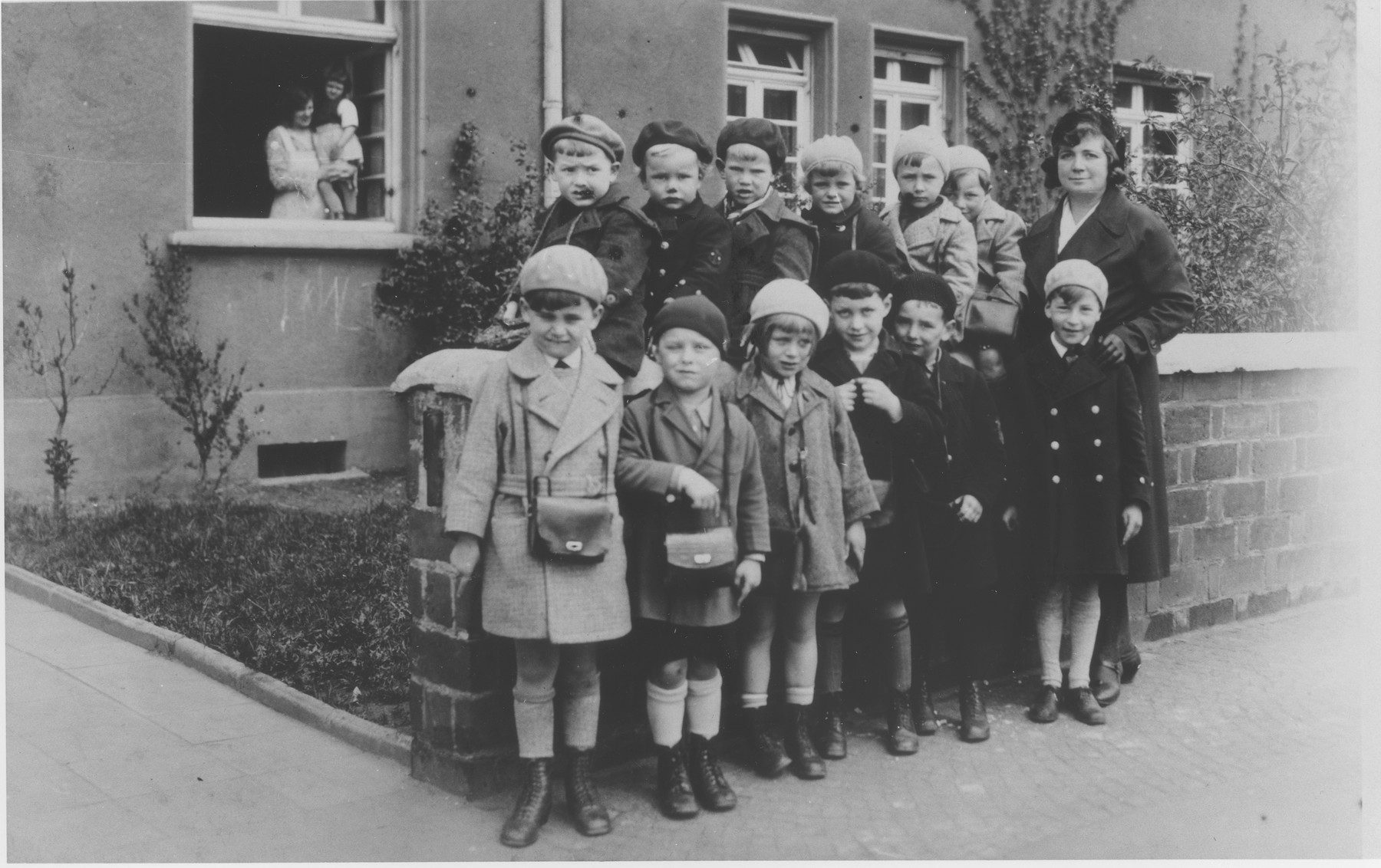 Pupils of the Jüdische Volksschule pose in front of the school on Lutzowstrasse in Köln.  Among those pictured is Manfred Loeb (standing in front of the teacher).