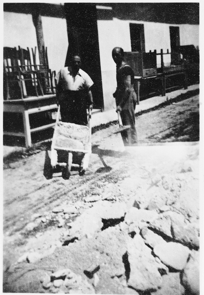 Two Jewish prisoners transport heavy rocks in a wheelbarrow in a Slovak labor camp.  One of those pictured is Emil Mittelman.