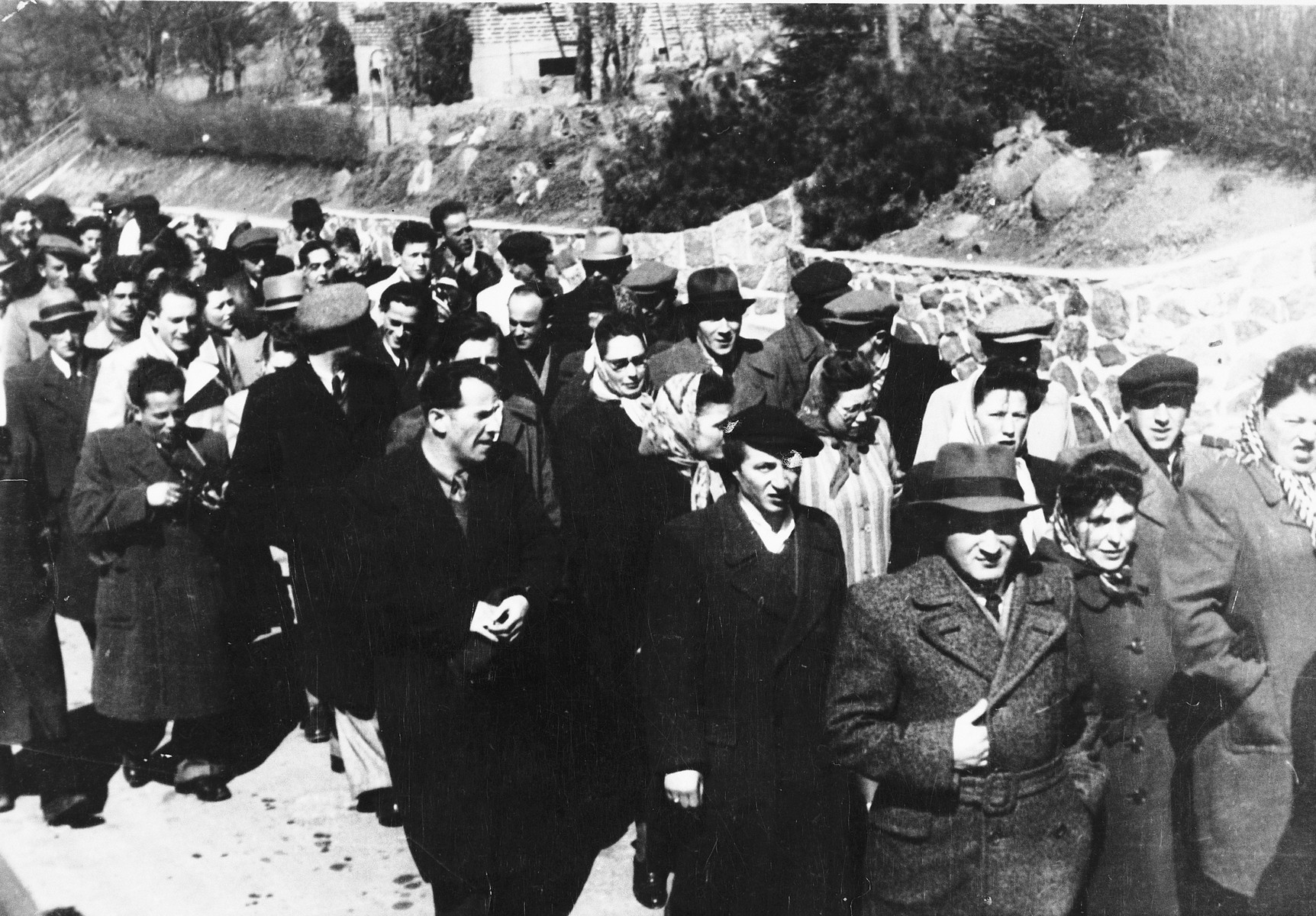 Jews from the Neustadt displaced persons camp, some wearing concentration camp uniforms, march to a memorial service.