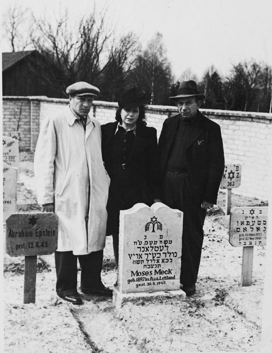 Three displaced persons pay their respects next to a grave in the Jewish cemetery in Neustadt.  Natan Roloff is on the right.