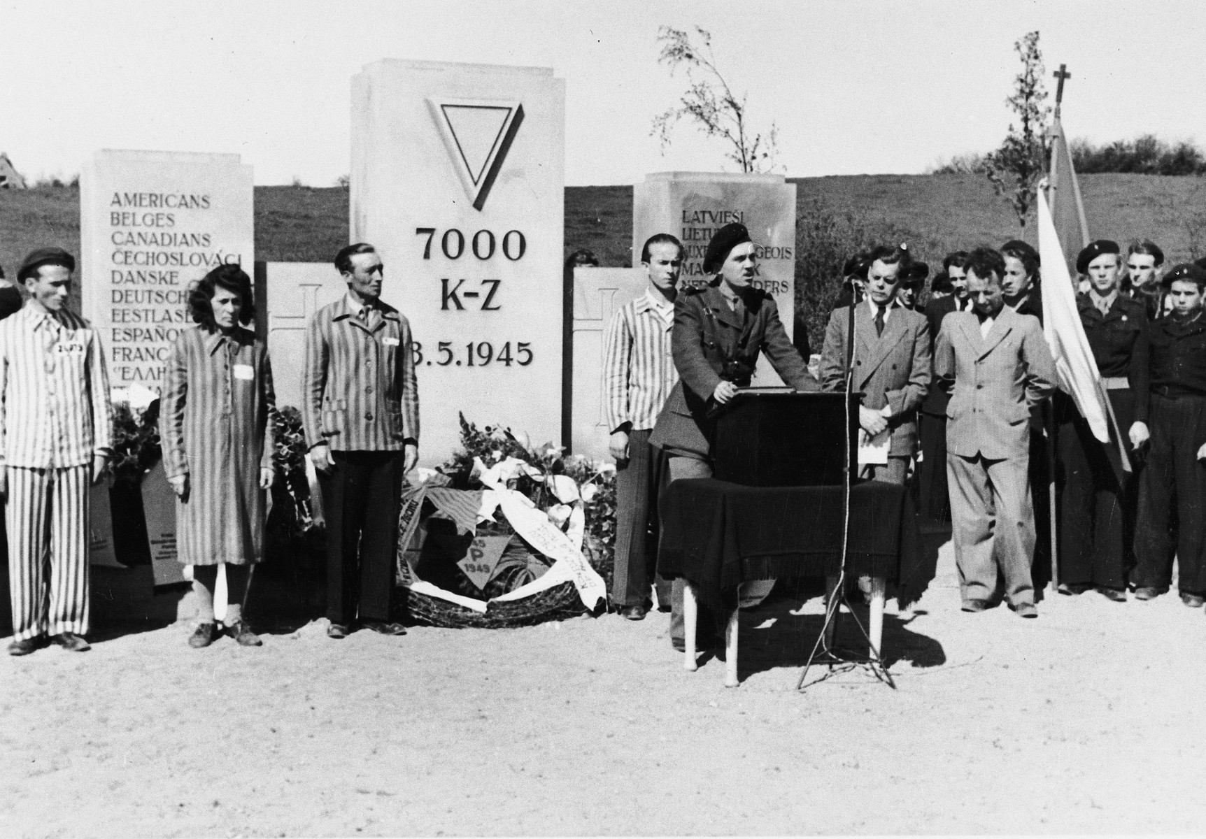 Jewish displaced persons, many wearing concentration camp uniforms, attend a memorial service for the 7000 prisoners who perished in Neustadt.
