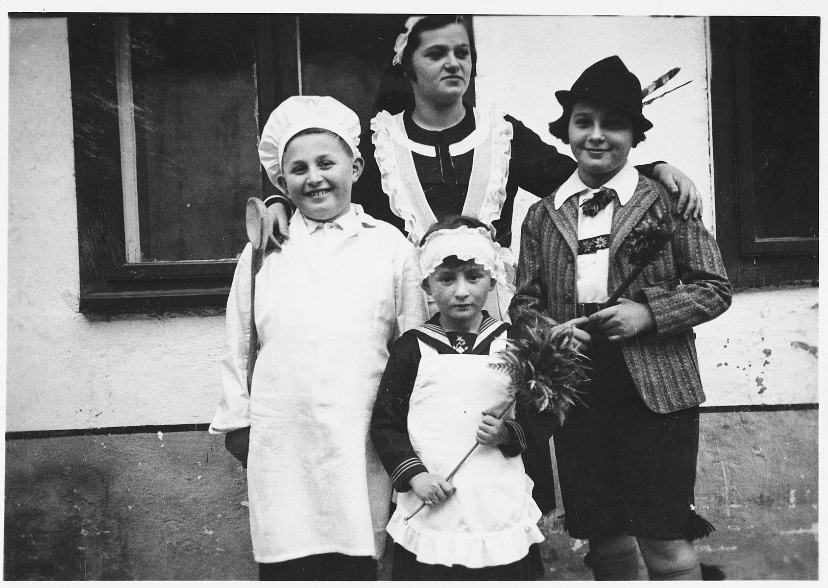 Four Jewish children pose together in their Purim costumes.  Josef Mittelman, dressed as a chef, is on the far left.  His brother Erwin is dressed as a maid, and their two older cousins are to their right.