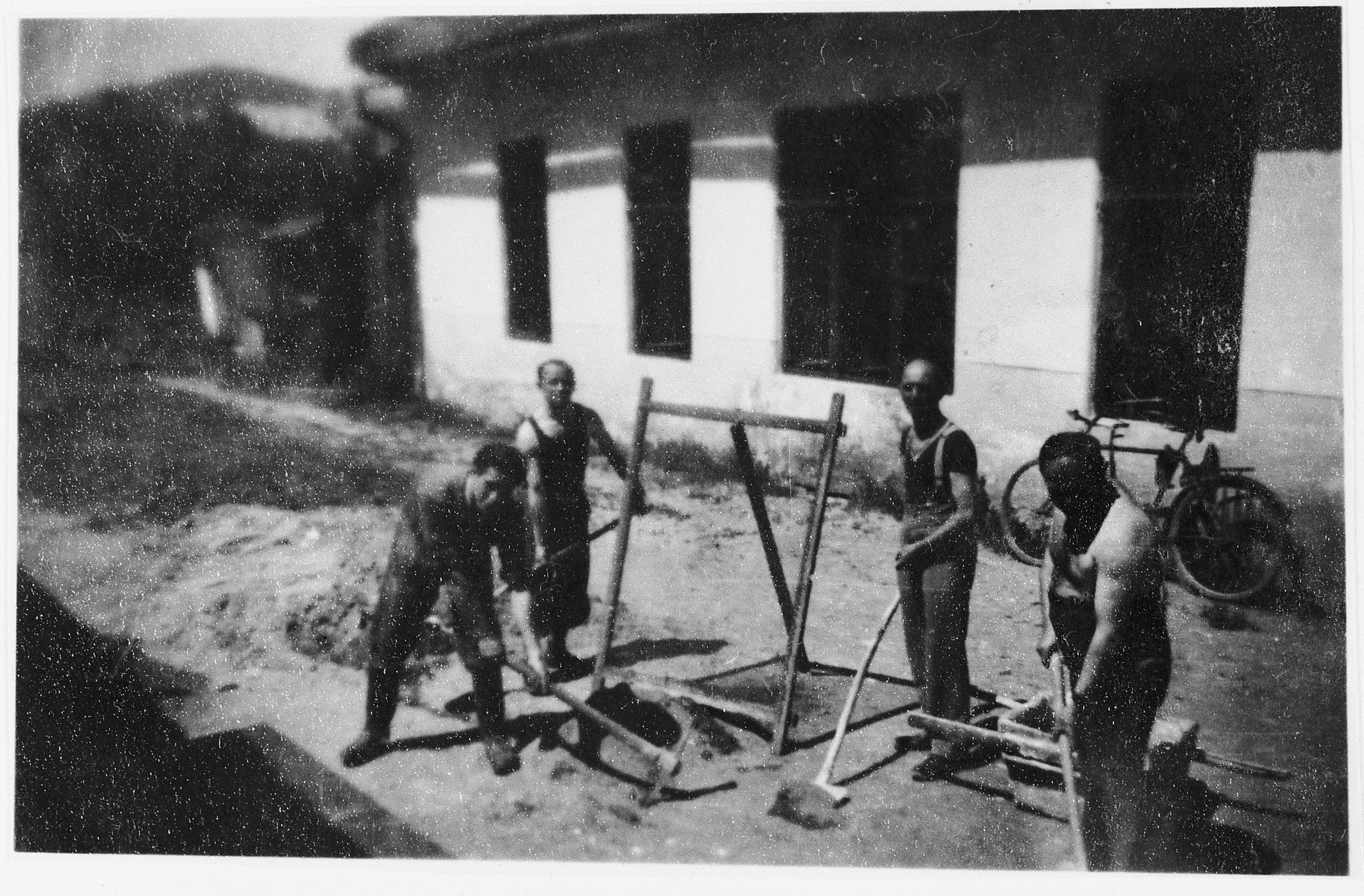Four Jewish prisoners work outside a barracks in a Slovak labor camp.  One of those pictured is Emil Mittelman.