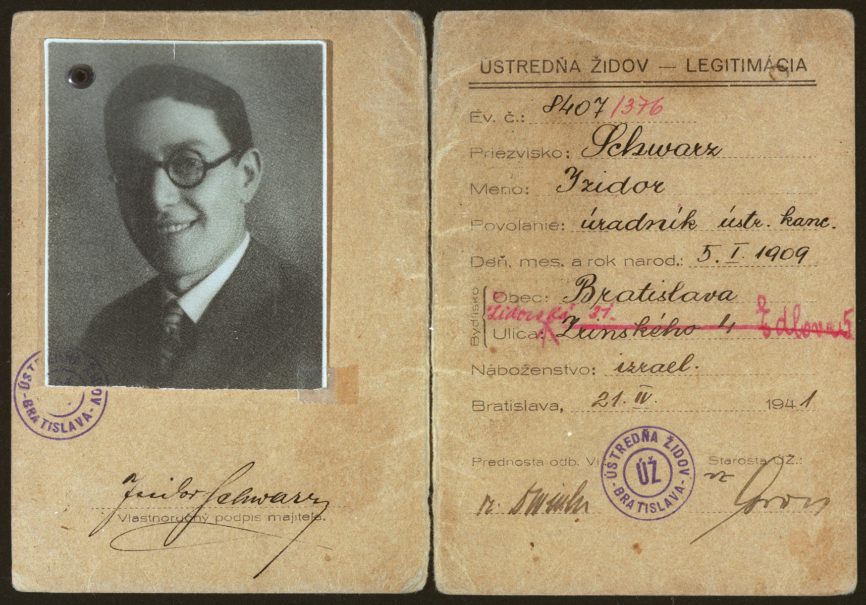Interior pages of an identification card issued by the Ministry of the Interior to Izidor Schwarz stating that he is an office worker employed in the main office of the Jewish community.