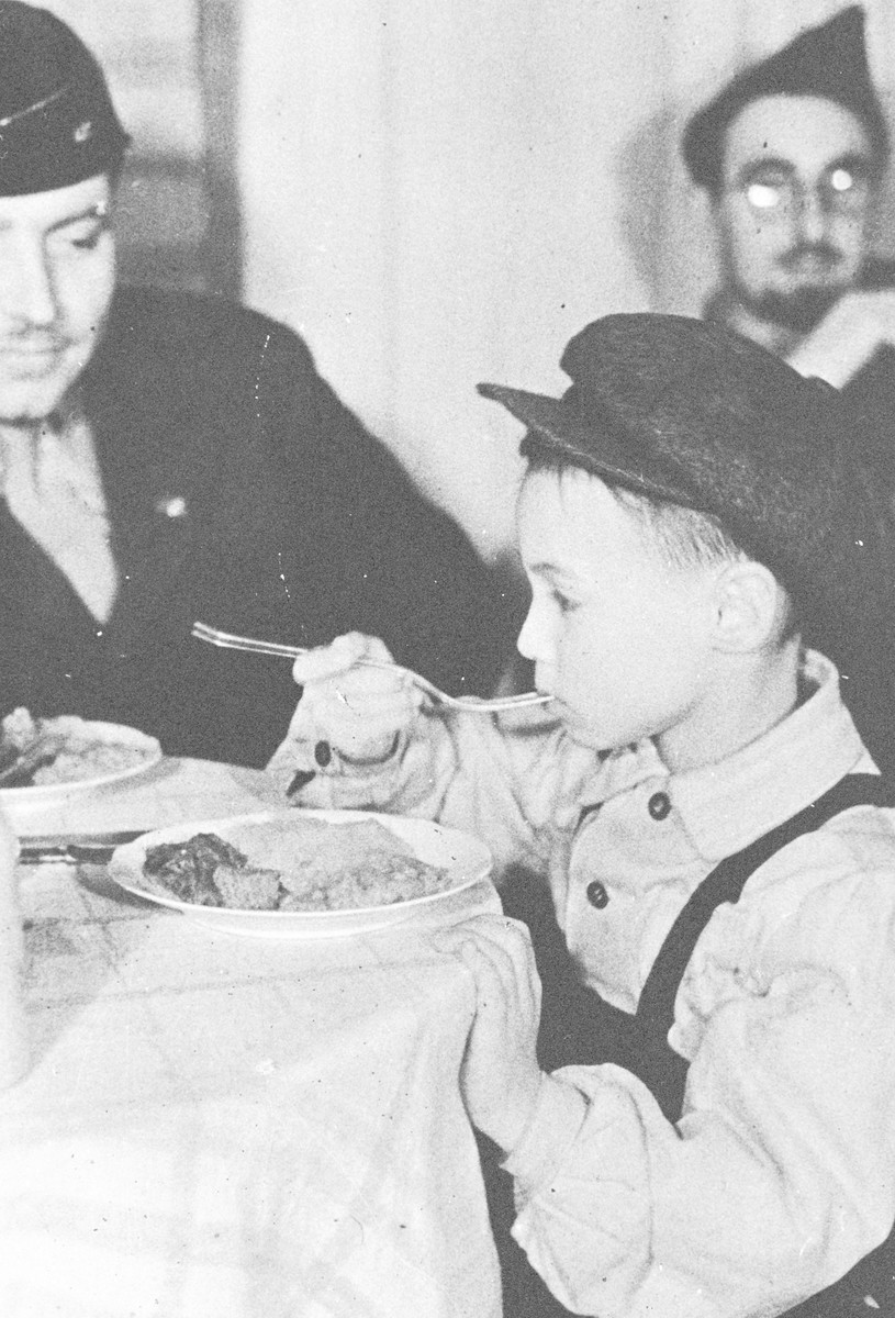 Rabbi Nathan Baruch and Rabbi Aviezer Burstein watch a young child eat at the kosher kitchen in the Dachau displaced persons' camp.