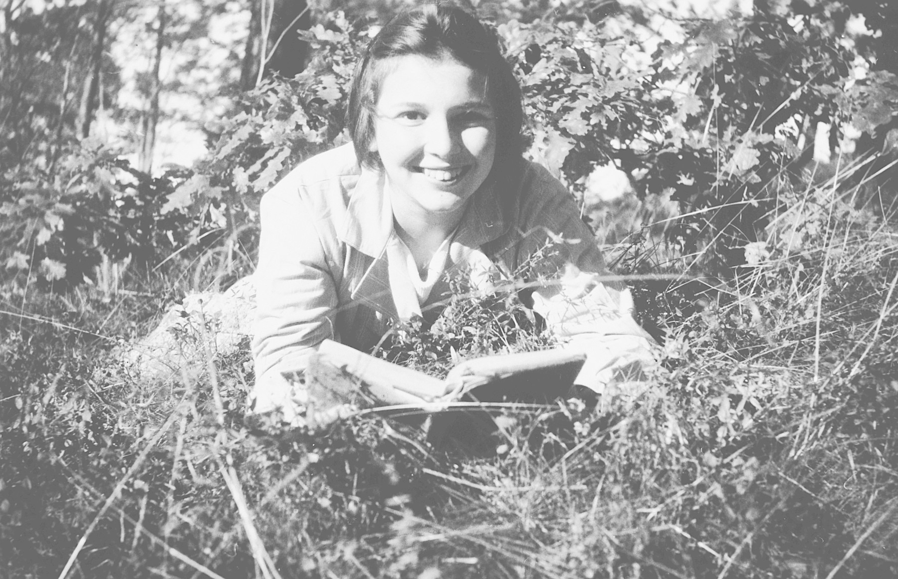 "Helga Arndtheim reads in the grass at a convalescent home in Sweden.   On the back of the photo, she says in German ""To my beloved Aunt Paula from her niece Helga."""