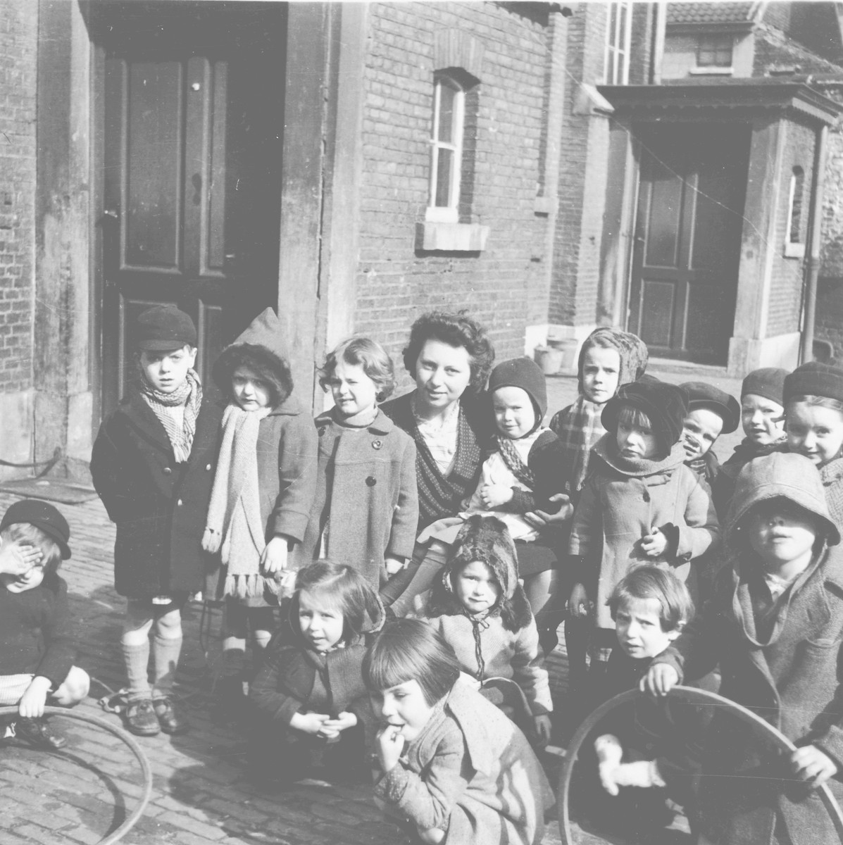 Jeanne Daman (center) poses with Jewish children under her care in the Nos Petits kindergarten.