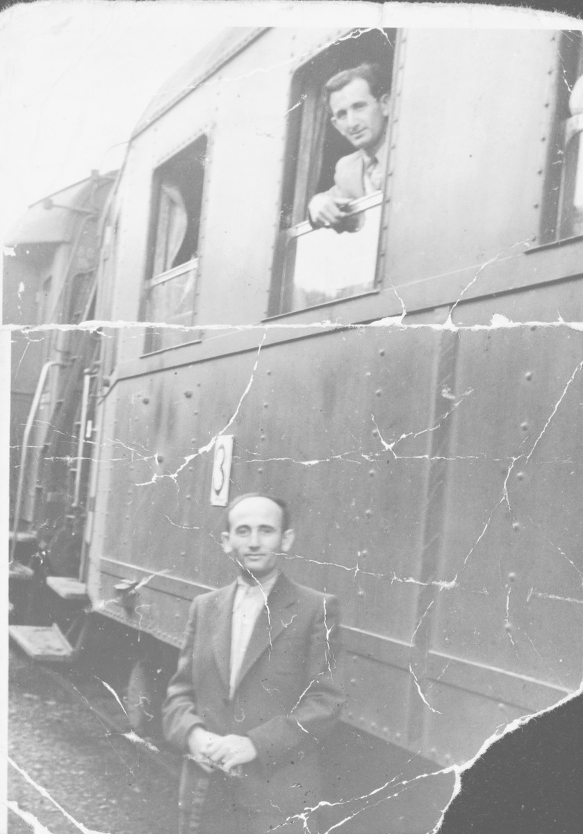 Two brothers pose in and outside a train [possibly in Muehldorf].  Pictured looking out of the train window is Simon Ruder.  Standing next to the train is his brother Mendel.