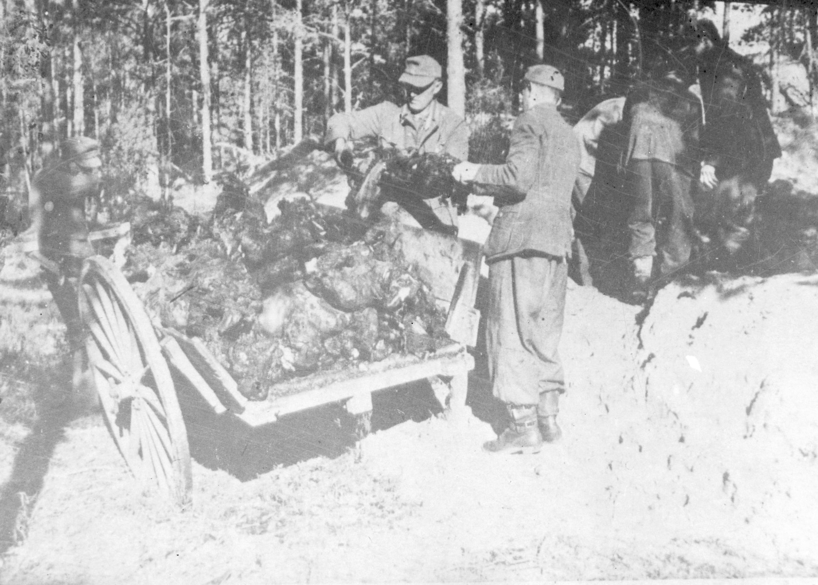 [Former prison guards] exhume and rebury charred corpses in the Klooga concentration camp following its liberation by the Soviet Union.