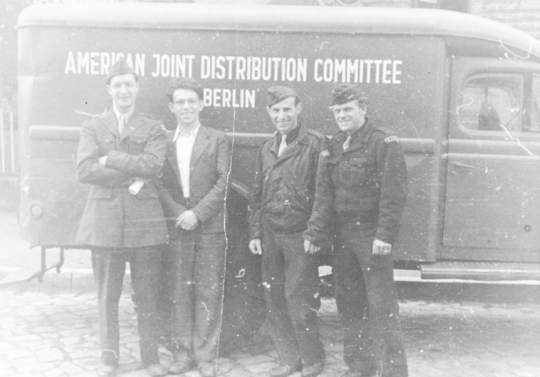 Four aid workers stand in front of an American Joint Distribution Committee truck in Berlin.  Heinz (now Henry) Rusheen is at the far right.  Himself a DP, he had been in the Riga ghetto and Stutthof concentration camp.