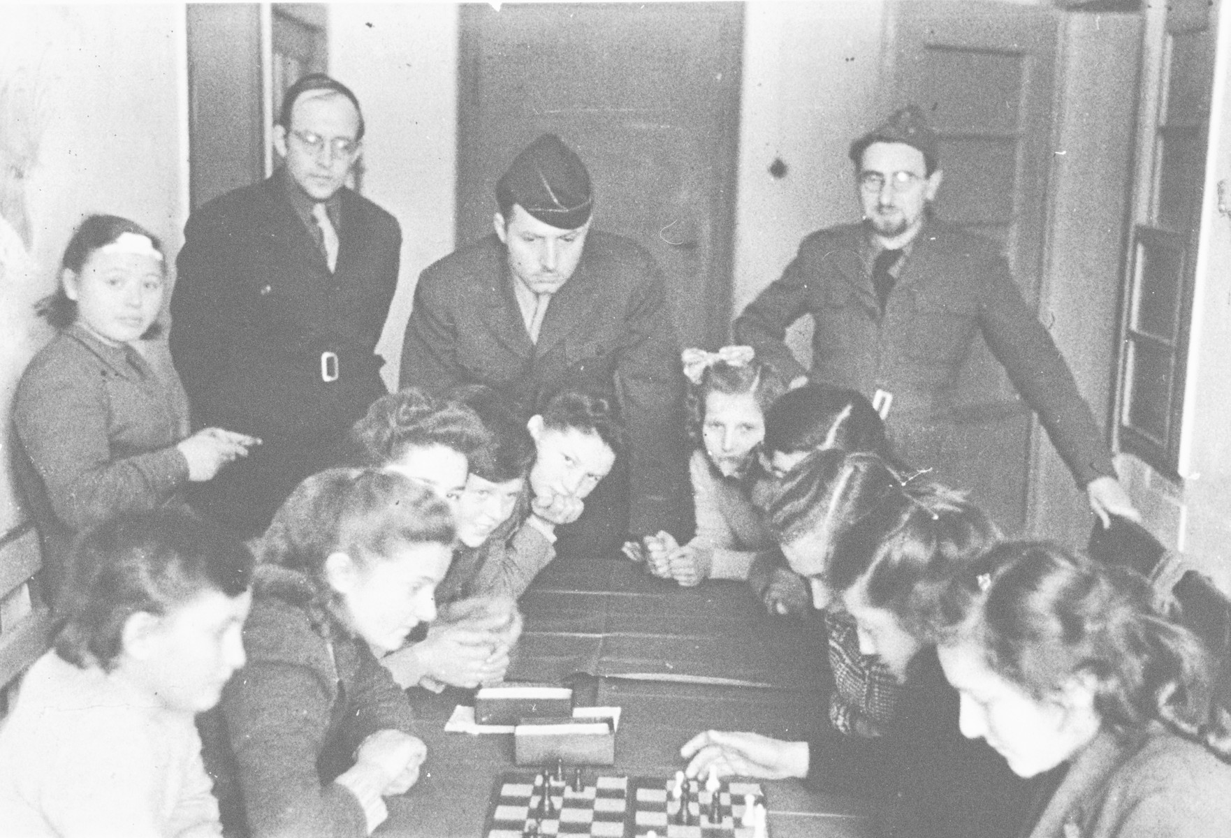 School girls play chess in the Poalei Agudat Yisrael children's home in Ulm run by the Vaad Hatzala while Vaad rabbis look on.  Rabbi Nathan Baruch is in the center and Rabbi Aviezer Burstin is standing on the right.