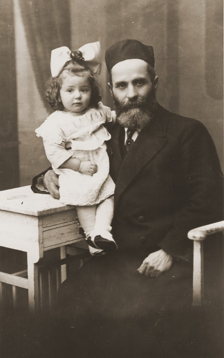 Studio portrait of a Jewish grandfather holding his granddaughter.  Pictured is Yechezkel Turetsky and his granddaughter, Rivka Radzinski.