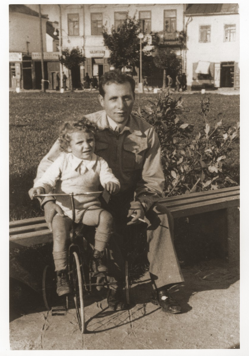 Usher Rosenzweig helping his son Izhak on a tricycle.
