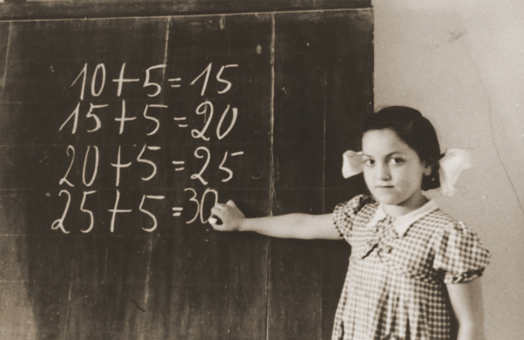 A young girl writes mathematics problems on a school chalkboard in the Neu Freimann DP camp.