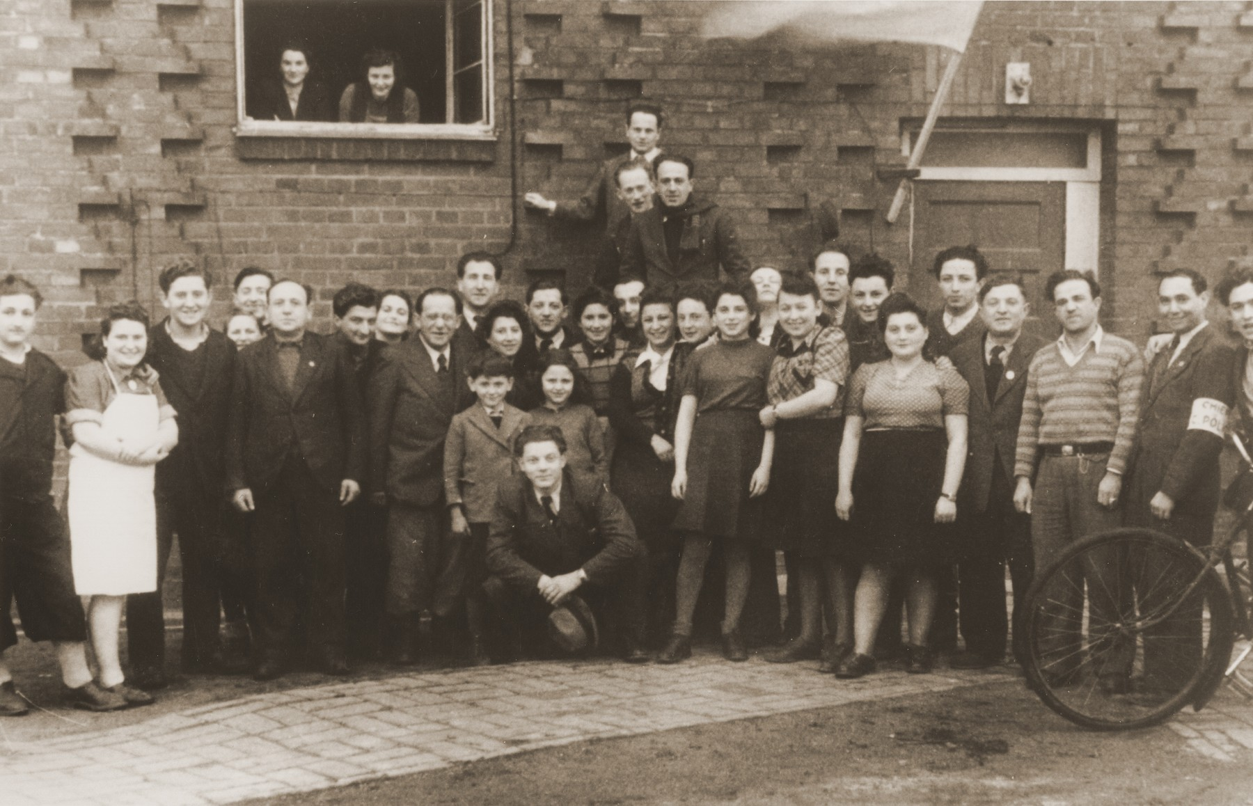Administrative staff of the Vinnhorst displaced person's center.  Among those pictured is Jacob Stefan Rue, squatting in the center of the group.  Also pictured is Henryk Arfa, the second person (tall male) to the left of the door.