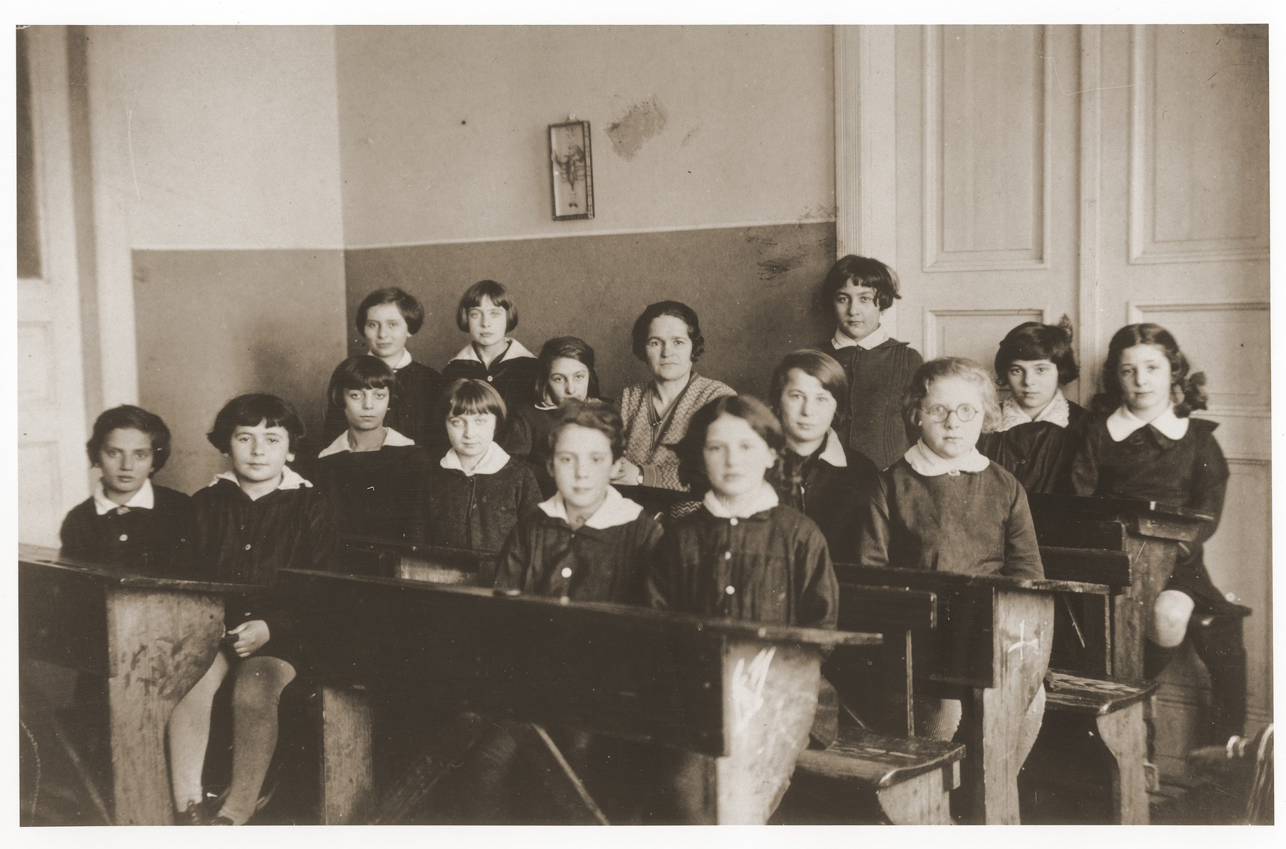 Students are seated at their desks in a classroom at the Chawatselet Jewish gymnasium for girls in Warsaw.  Among those pictured is Rivka Radzinski (first from the right).