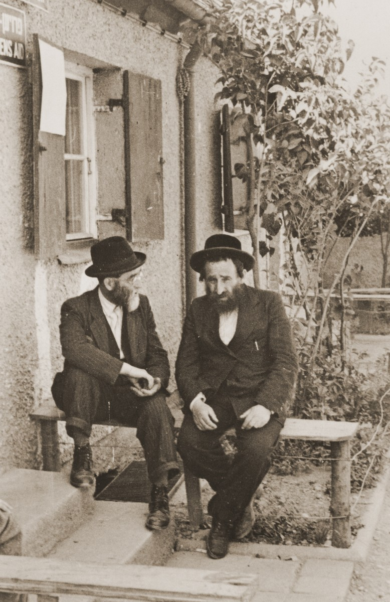 Two religious Jewish DPs sit outside a welfare office in the Neu Freimann displaced persons camp.