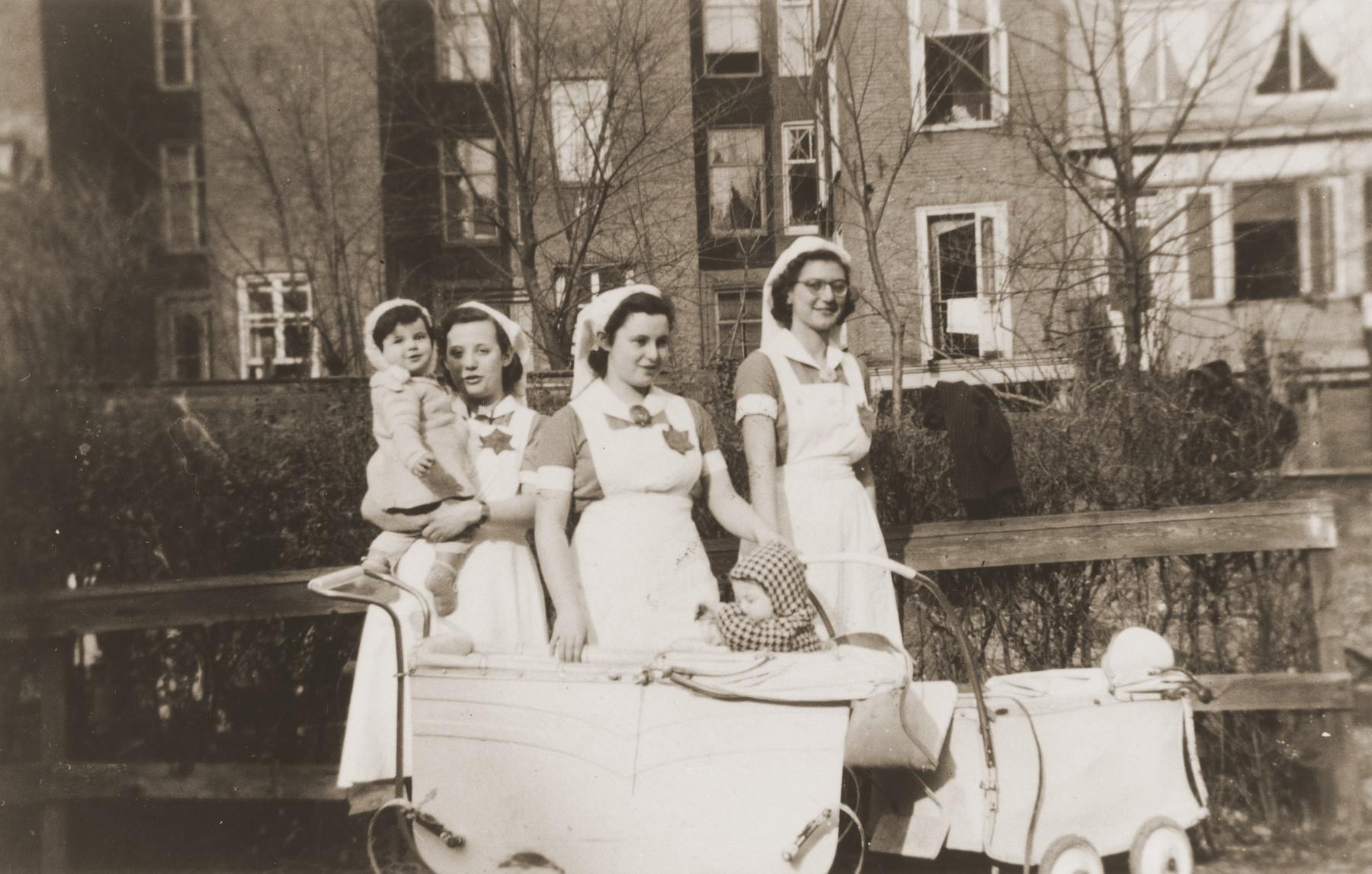 Three childcare workers wearing Jewish badges take three young children for a stroll in the Amsterdam Jewish quarter.  Pictured from right to left are childcare workers, Hilde Jacobsthal, Margot Herz and Margot Stern.
