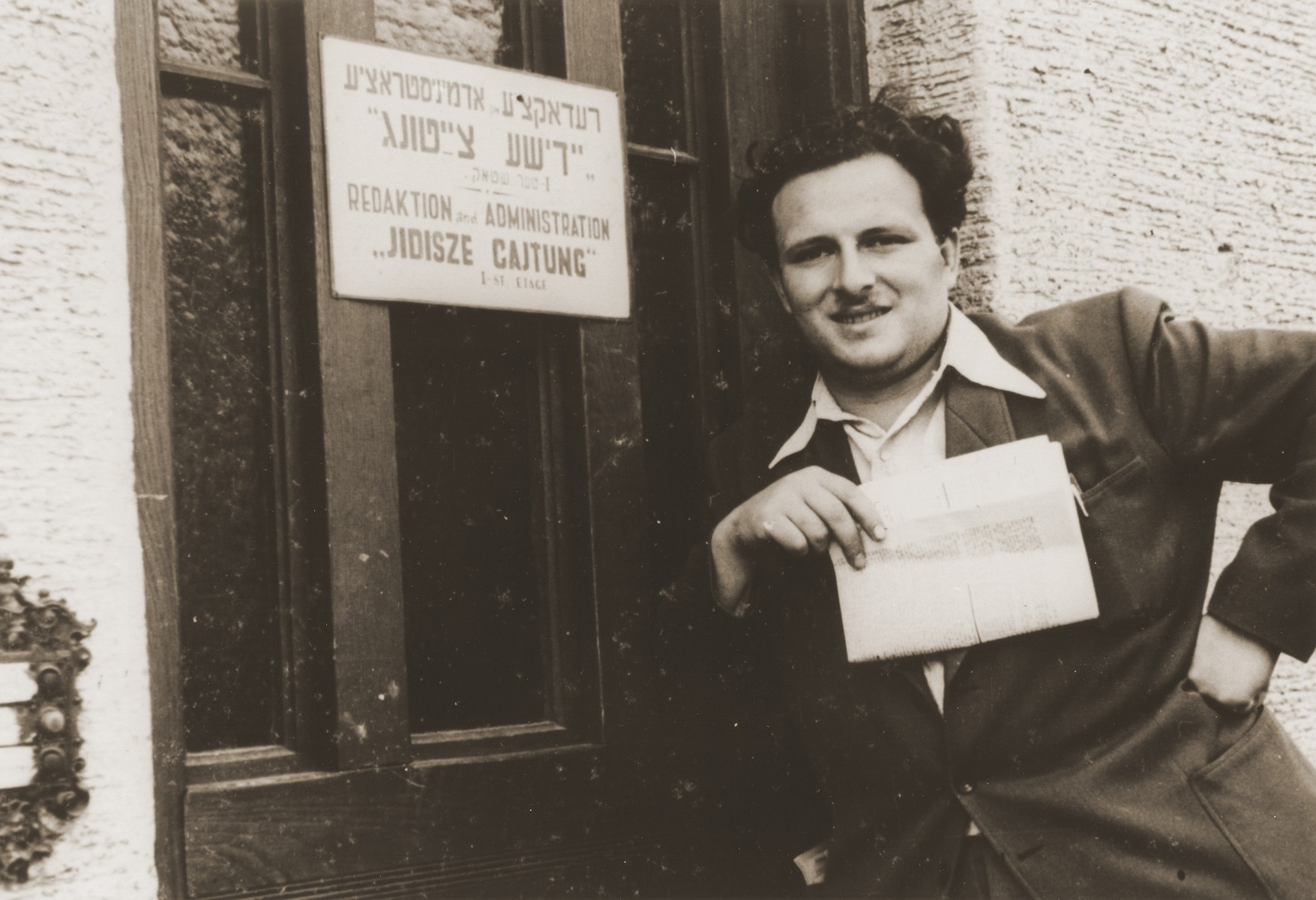 "Izik Sutin stands in front of the ""Jidisze Cajtung"" newspaper office in the Neu Freimann displaced persons camp."