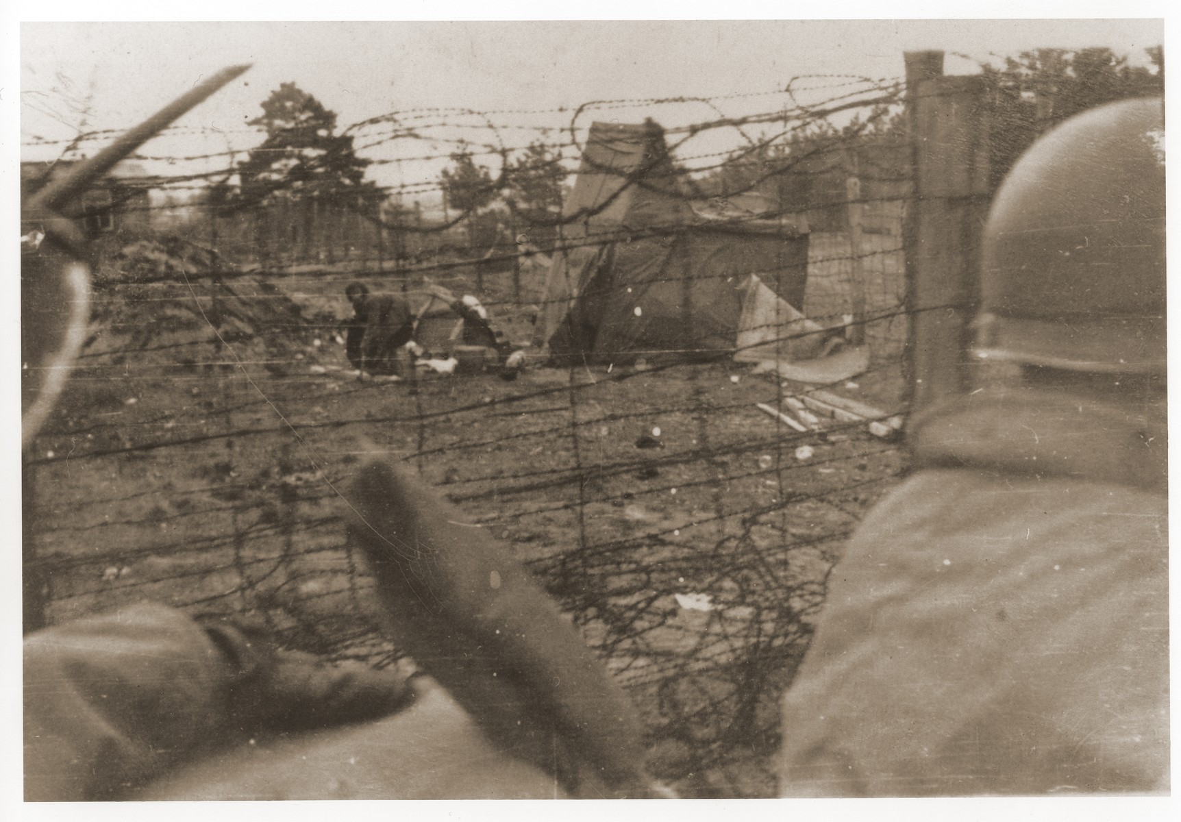 American troops with the 42nd Tank Battalion drive along the fenced-in perimeter of the Bergen-Belsen concentration camp.  The 42nd was part of the 7th Armored Division, which was the only American unit attached to the British Second Army, the unit that liberated Bergen-Belsen.