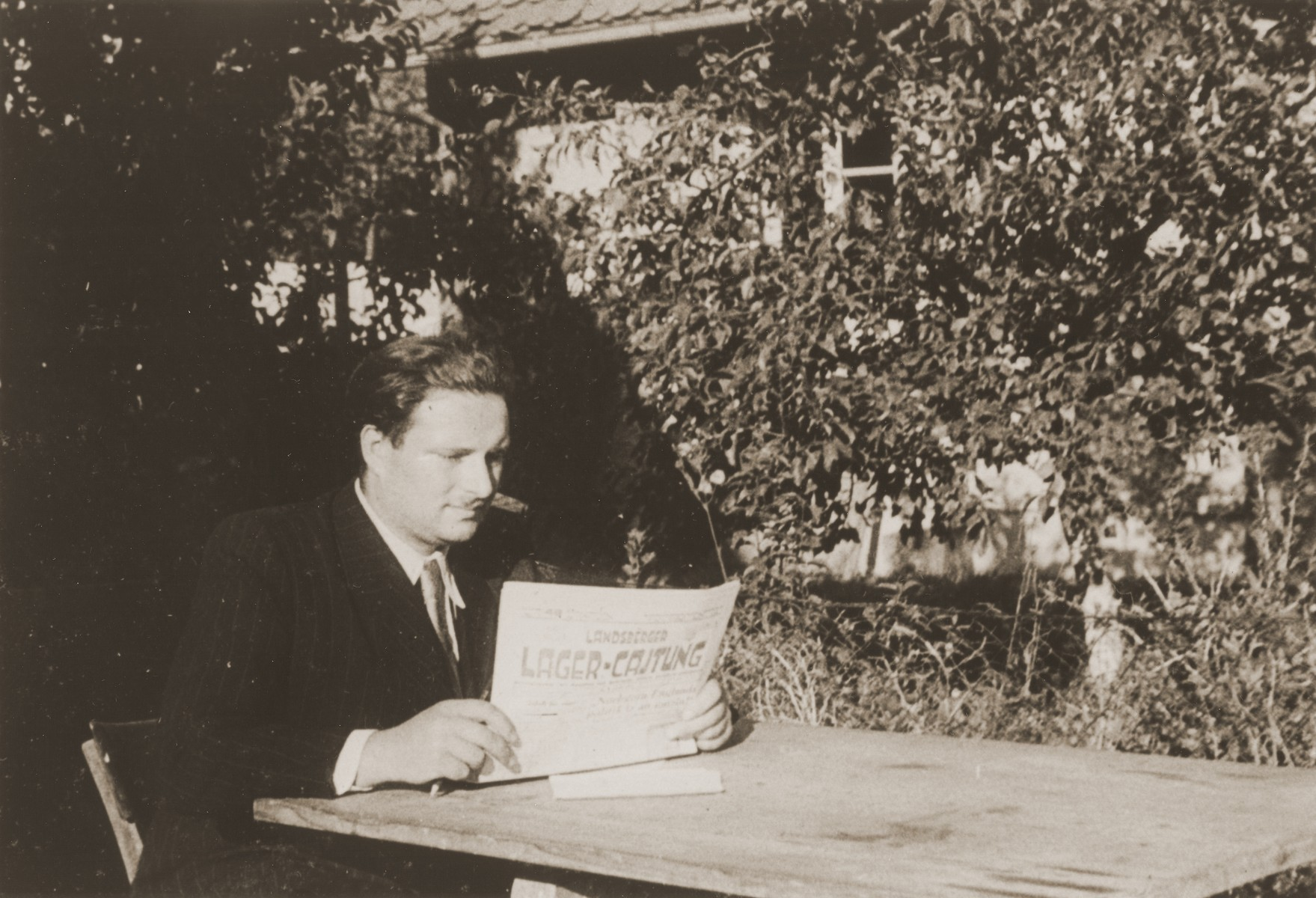 Photojournalist Izik Sutin reads the Landsberger Lager-Cajtung, a newspaper to which he was a frequent contributor.