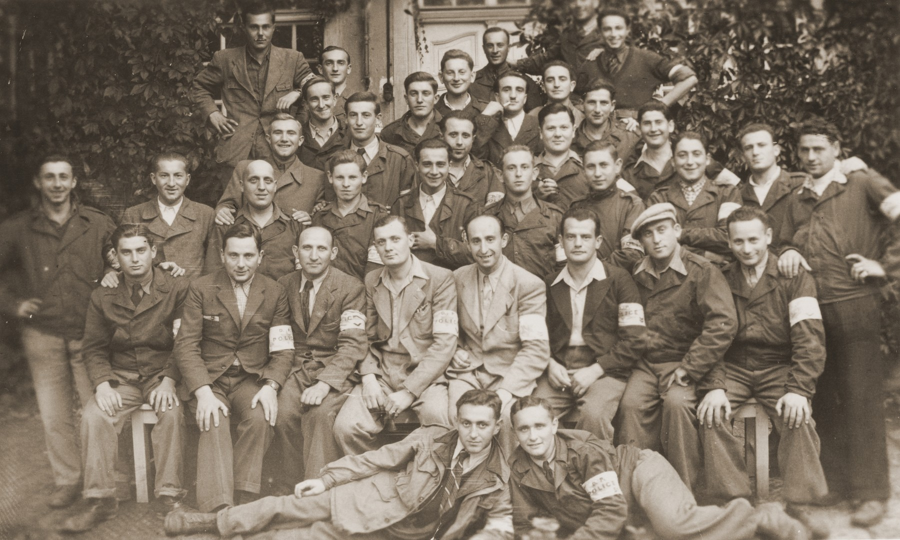 Group portrait of Jewish police in the Landsberg displaced persons camp.  Among those pictured is Moshe (Morris) Barkowski, in the third row (first row standing), fifth from the left.