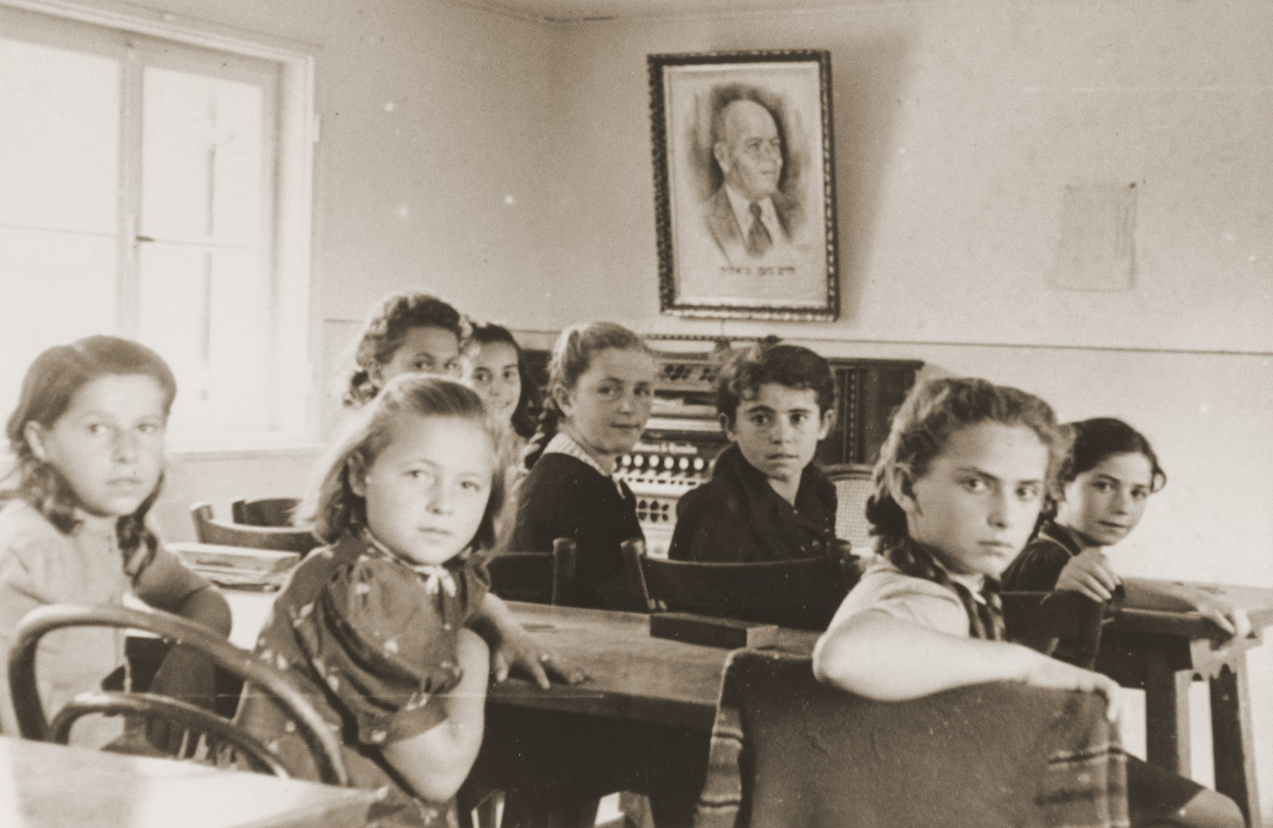 Pupils sitting at tables in a classroom in the Neu Freimann displaced persons camp.