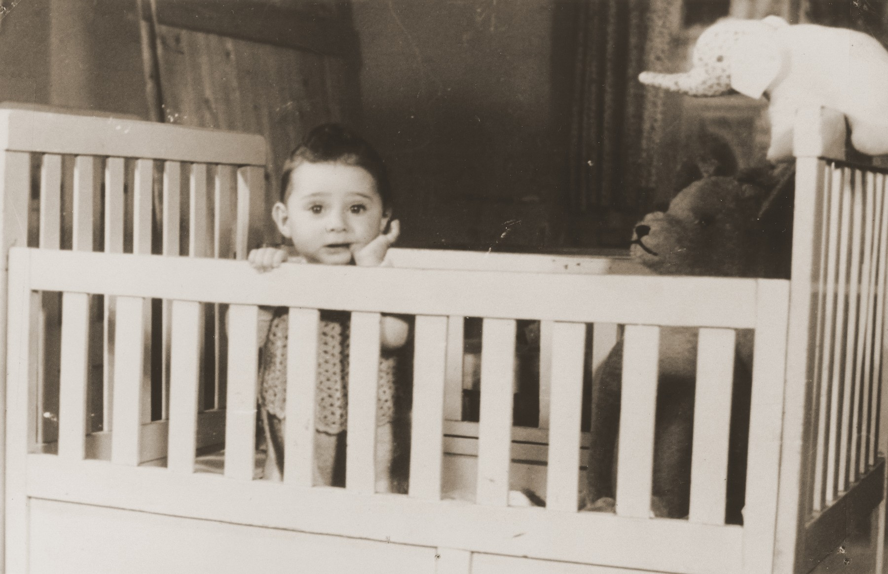 Remi Van Duinwijck, a young Jewish boy stands in his crib in the childcare center at the Joodsche Schouwburg in the Amsterdam Jewish quarter.