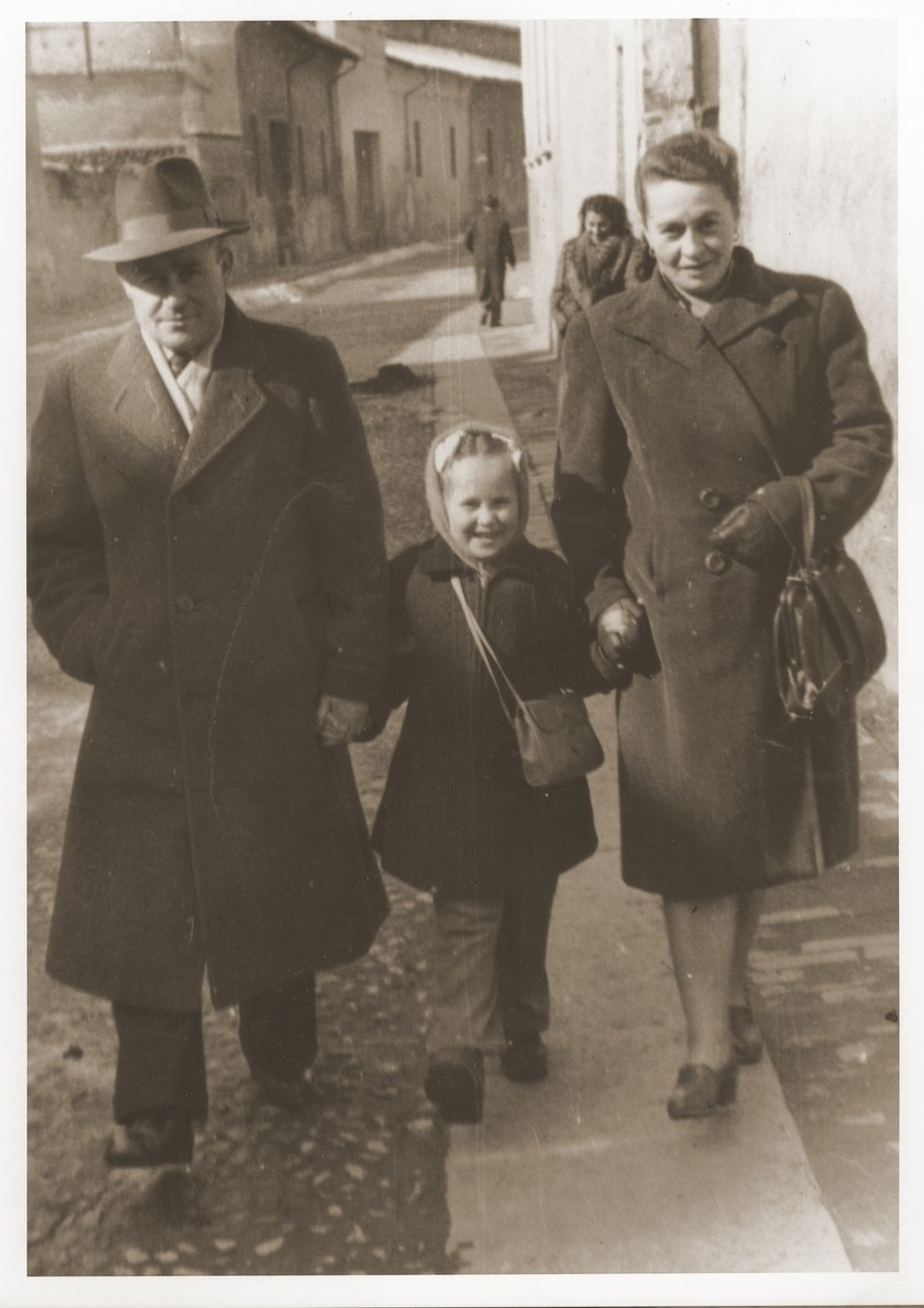 A Jewish DP family walks along a street in Cremona.  Pictured are Motel, Zelda and Masha Leikach.